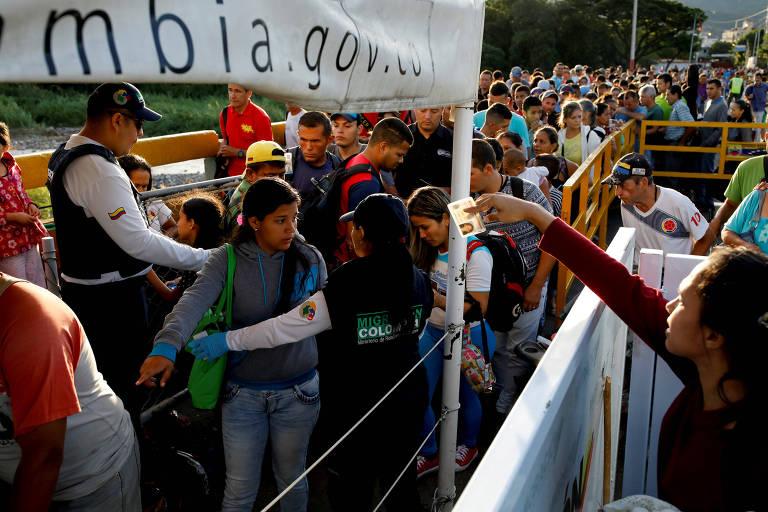 Agente de imigração levanta braço com carteira de identidade na mão para entregar a outro agente. Do outro lado de uma grade, aparecem homens e mulheres sendo revistados à frente de uma fila com centenas de pessoas.