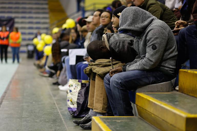 Grupo de dez pessoas espera sentado em arquibancada de cimento de ginásio.