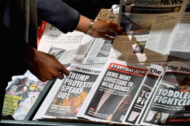 Ação da Faculdade de Jornalismo da Universidade Columbia mostra notícias falsas em jornais de papel em uma banca de Nova York