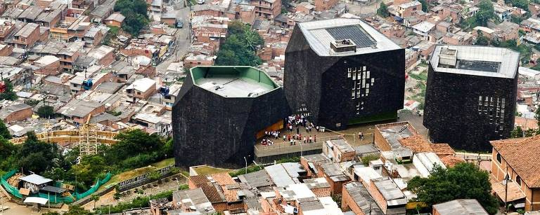 Biblioteca España, na cidade colombiana de Medellín, onde unidades como esta colaboraram para alterar índices de criminalidade; prédios da biblioteca parecem grandes rochas negras, enormes contra o panorama da favela onde se localizam, no alto de um morro