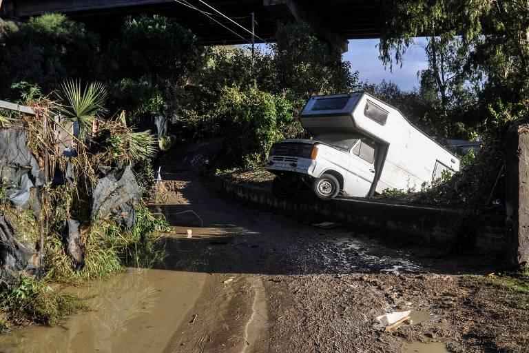 Um estrada de terra com poças de água depois de chuvas fortes, que arrastaram um motorhome, que aparece capotado, à direita