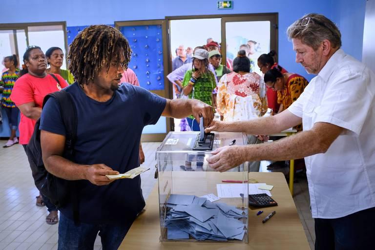 Homem coloca seu voto em uma urna transparente para decidir sobre a independência da Nova Caledônia, arquipélago no Pacífico