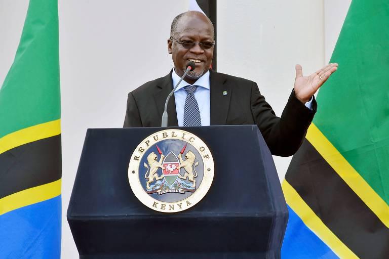 Entre duas bandeiras coloridas, o presidente da Tanzânia faz um discurso em uma tribuna
