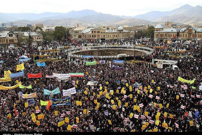 Multidão com cartazes amarelos se reúne em frente à antiga embaixada americana, que foi ocupada por iranianos anos atrás