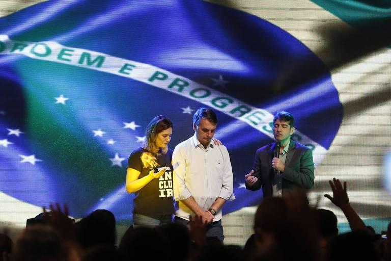Um telão exibe uma enorme bandeira do Brasil. Diante dela, o presidente e a primeira-dama oram de cabeça abaixada, enquanto um pasto fala ao microfone