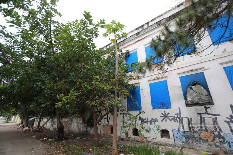 Casa branca com tapumes azuis nas janelas