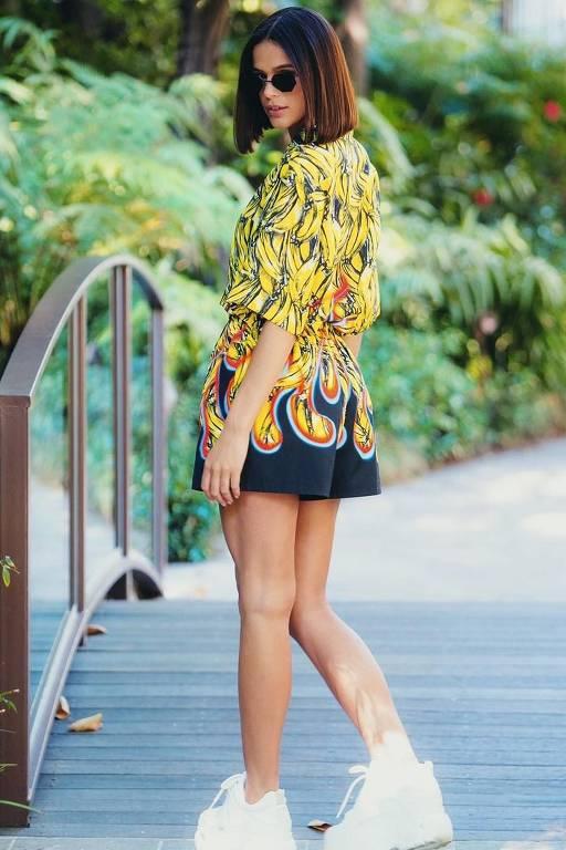3a9fbed3b Bruna Marquezine exibindo as pernas em um macacão estampado com tênis  branco ...