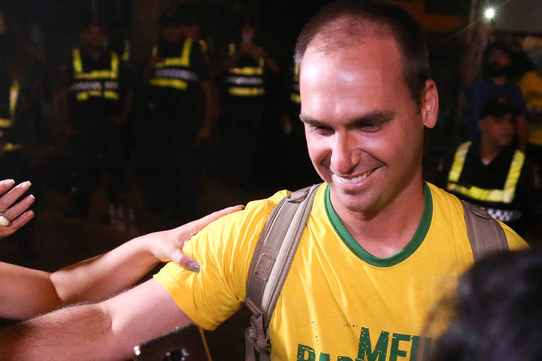 Com uma camiseta amarela, Eduardo Bolsonaro tira foto com várias pessoas