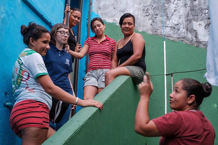 Seis mulheres aparecem na imagem, sendo um apontando o dedo para cima à direita e cinco se espalhando por uma escada de cor verde. A casa tem paredes azuis.