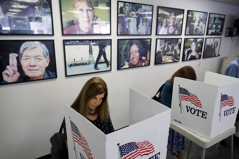 Duas mulheres aparecem vistas de cima em cabinas de votação brancas, que têm a bandeira dos EUA e a palavra vote. Na parede ao fundo, diversas fotografias em quadros.