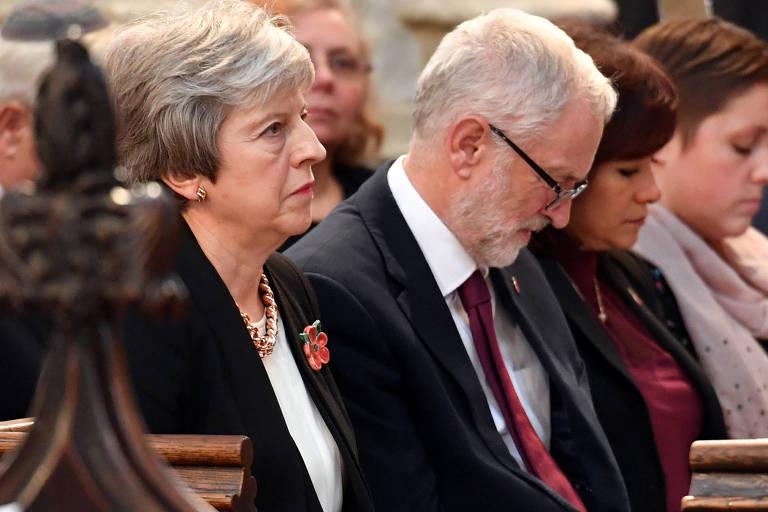 Theresa May ao lado do líder do oposicionista Partido Trabalhista, Jeremy Corbyn, durante cerimônia em igreja de Londres
