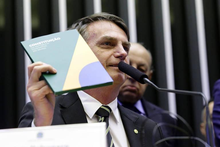 Bolsonaro fala diante de um microfone e segura o livro com a mão esquerda