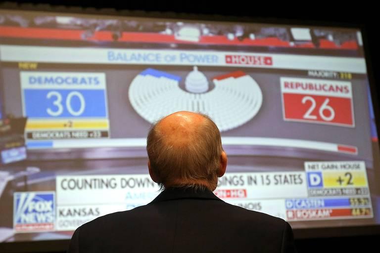 Homem aparece de costas, enquanto vê a tela.