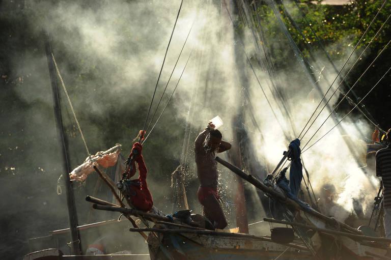Homem se banha em cima de embarcação no mar. Ao fundo, há árvores, parcialmente encobertas por uma forte fumaça