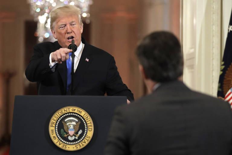 De um púlpito, Trump aponta o dedo para o jornalista, que aparece de costas