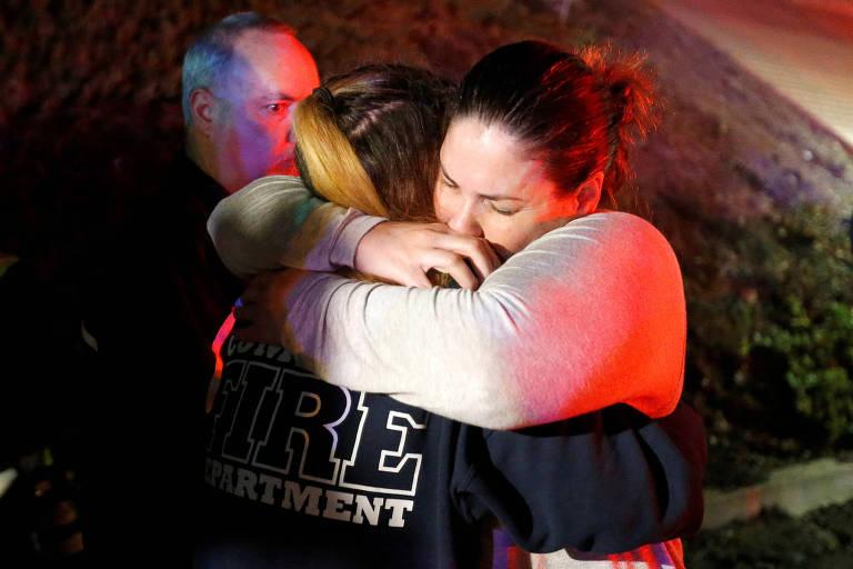 Mulheres se abraçam do lado de fora do bar