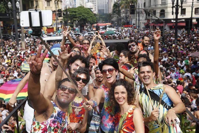 """Foliões tiram foto com """"pau de selfie"""" durante desfile do bloco """"Tarado Ni Você""""  na avenida Ipiranga com a Avenida São João, no centro de São Paulo"""