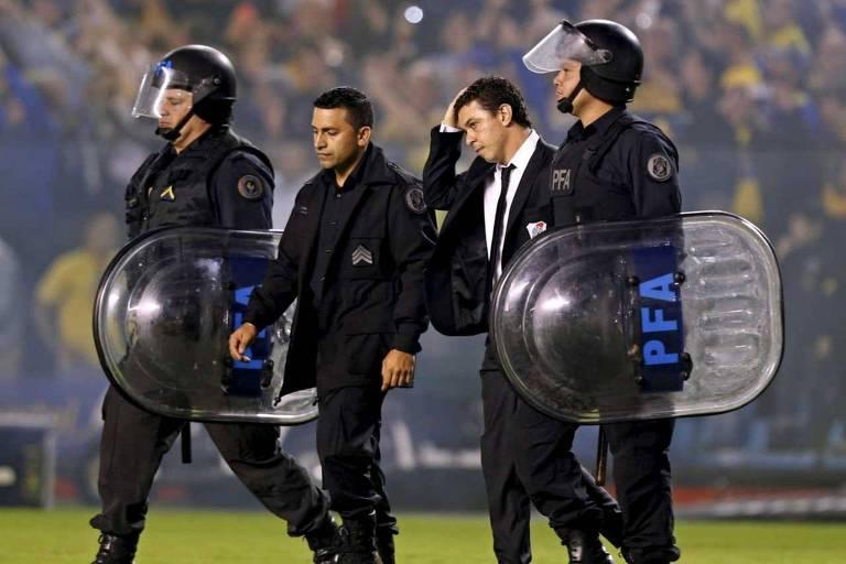 O técnico Marcelo Gallardo, do River Plate, é escoltado por policiais no gramado da Bombonera