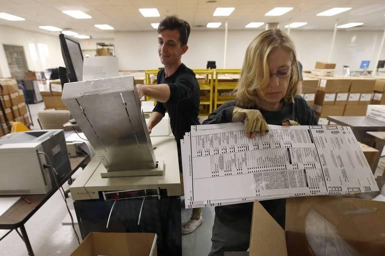 Homem coloca cédulas em uma pasta ao fundo, enquanto mulher está à frente organizando papéis. Os dois estão em uma sala com diversos arquivos.