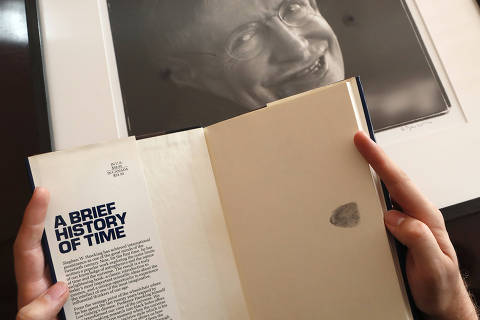 A Book, signed with a thumb print by Stephen Hawking is one of the personal and academic possessions of Stephen Hawking, photo behind, at the auction house Christies in London, Friday, Oct. 19, 2018.  The online auction announced Monday Oct. 22, 2018, by auctioneer Christie?s features 22 items from Hawking, including his doctoral thesis on the origins of the universe, with the sale scheduled for 31 October and 8 November.  (AP Photo/Frank Augstein) ORG XMIT: FAS114
