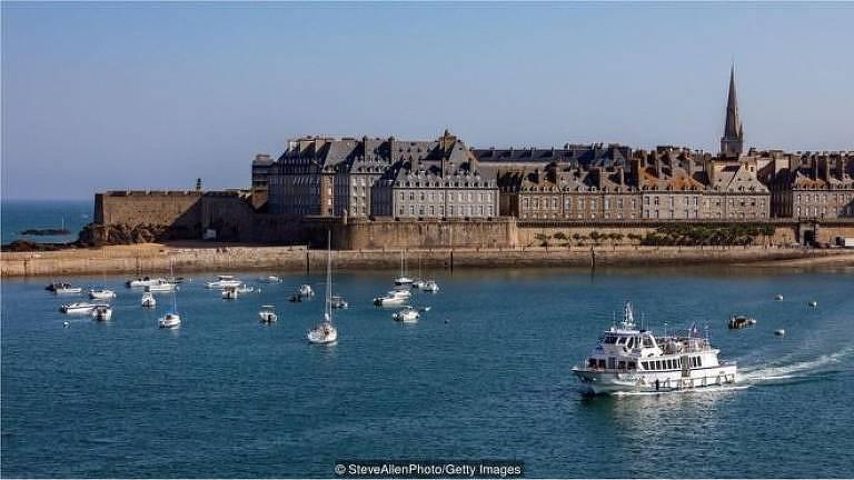 A imagem mostra a cidade de St-Malo, na França. Ela é uma pequena vila cercada por uma muralha e com prédios baixos e antigos. Ao redor dela, está o mar, onde há barcos navegando