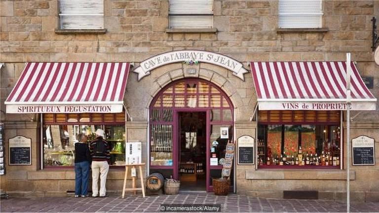 Fachada de loja de vinhos em St-Malo. O prédio é revestido de blocos de pedra. No centro, há uma porta grande e de vidro. Nos dois lados dela, há janelas largas e no topo delas, toldos com listras vermelhas e brancas