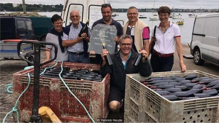 Um grupo de seis pessoas posa próximo a caixas envelhecidas, com garrafas de vinho no interior delas