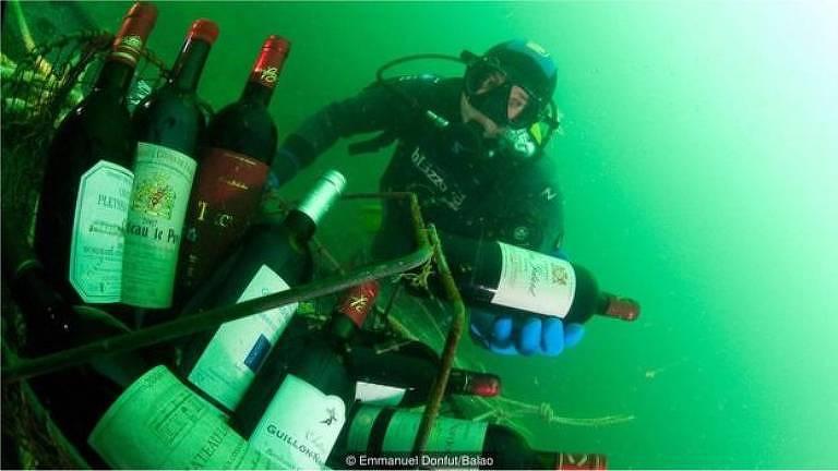 Mergulhador pega garrafas de vinho submersas no mar