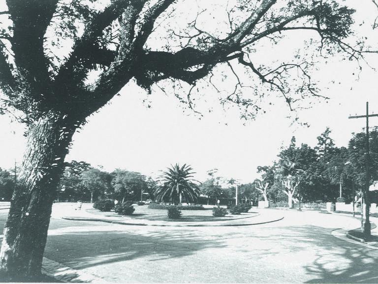 Foto em preto e branco de praça no Jardim América. Há uma rotatória para carros e diversas árvores na região