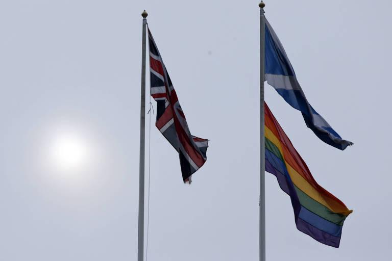 Bandeira britânica aparece no mastro à esquerda, enquanto no mastro à direita a bandeira escocesa aparece acima e a do arco-íris abaixo