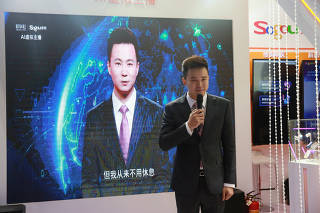 Xinhua news anchor Qiu Hao stands next to an AI virtual news anchor based on him, at a Sogou booth during an expo at the fifth World Internet Conference (WIC) in Wuzhen