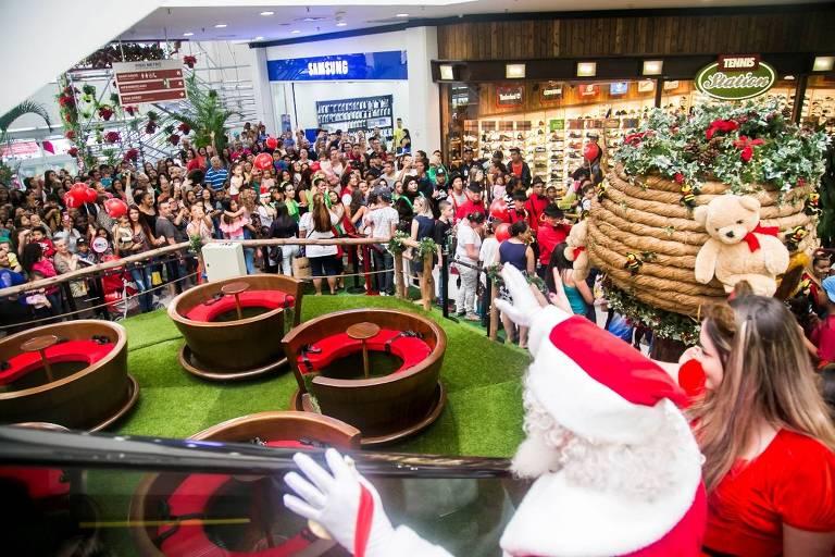 Na escada rolante, Papai Noel acena para o público no shopping Metrô Itaquera