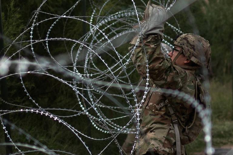 Soldado americano instala cerca de arame farpado em trecho da fronteira dos EUA com o México no Texas