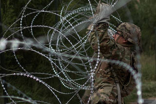 U.S. Army soldiers install concertina wire along the United States - Mexico border in Hidalgo, Texas