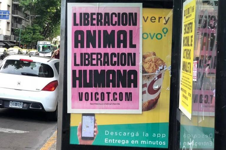Cartaz de ativistas veganos colado em cima de propaganda de fast-food de frango, em ponto de ônibus em Buenos Aires