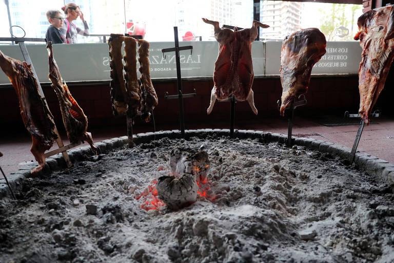 Nove grandes pedaços de carne em espetos verticais assam fincados no meio de carvão e brasas em uma vitrine diante da qual transeuntes passam
