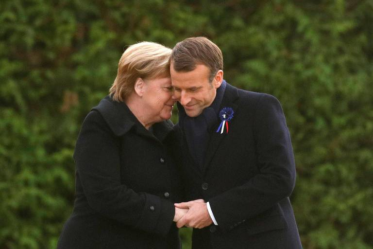 Merkel e Macron se abraçam. Os dois usam preto e estão em uma área arborizada.