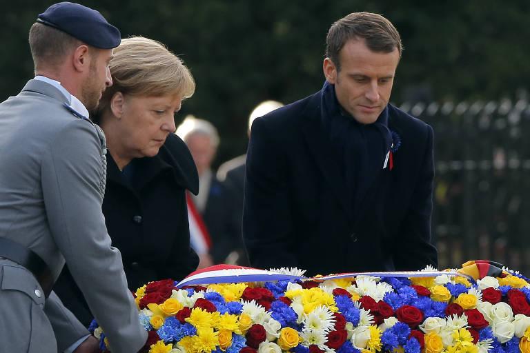 Merkel e Macron estão atrás da coroa de flores e têm a ajuda de um soldado