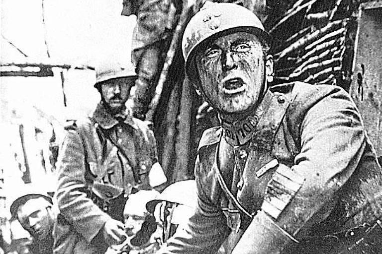 Soldado aparece com rosto franzido e boca aberta. Ao fundo, outros perfilados em uma trincheira