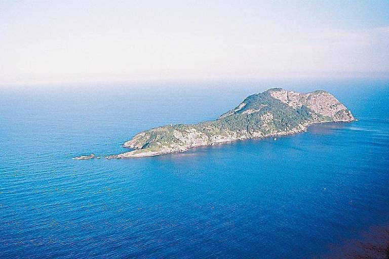Vista aérea da ilha, uma porção de terra comprida, estreita em uma ponta e alta na outra