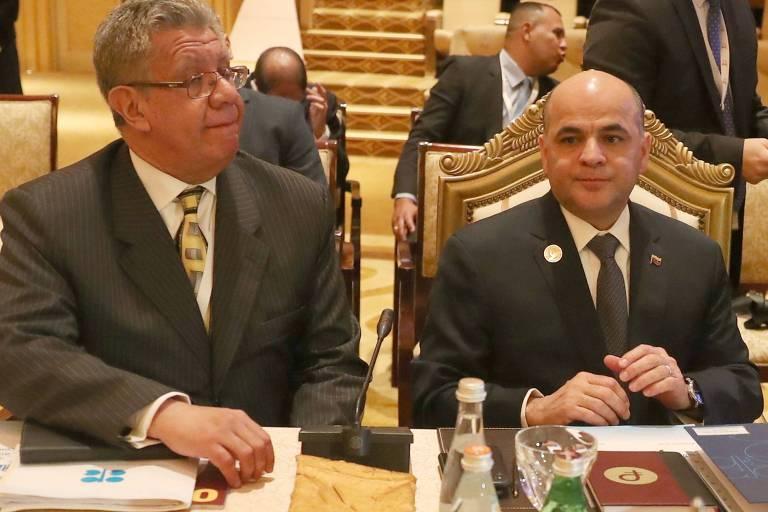 dois homens de terno em mesa de reunião com documentos e placas de nome