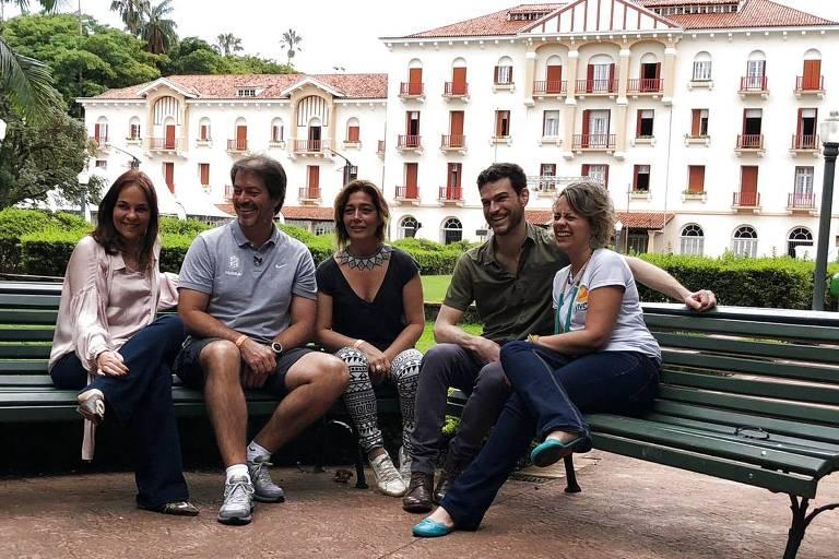 Cinco pesoas sentadas em bancos de praça com jardim ao fundo