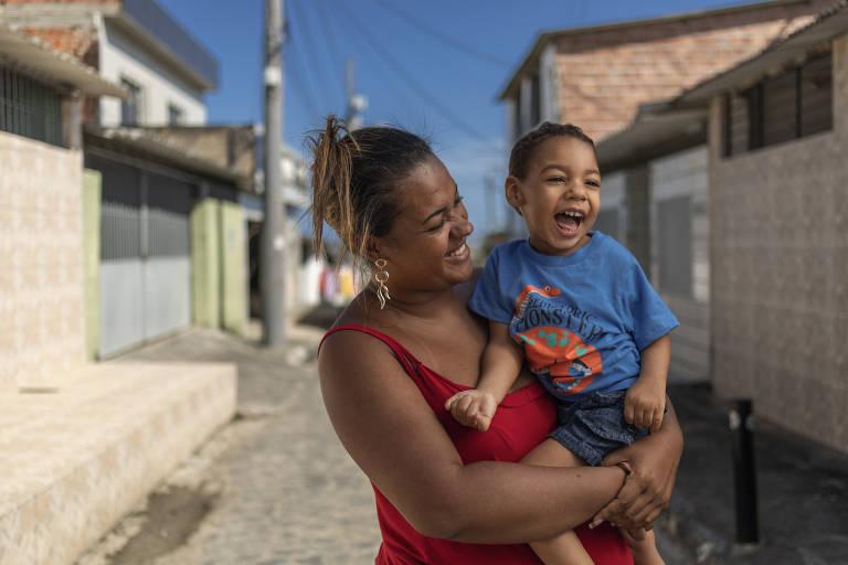 Germana Soares segura o filho Guilherme no colo; ambos sorriem