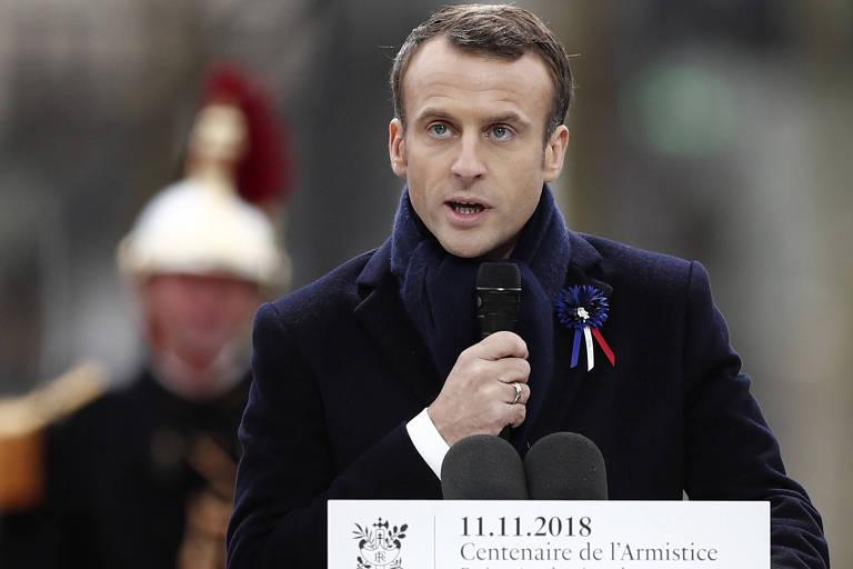 Macron segura um microfone enquanto fala em um púlpito. Ao fundo, um soldado vestido com um capacete dourado com uma pluma vermelha