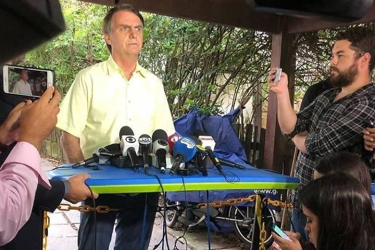 Microfones apoiados numa prancha durante entrevista coletiva na casa de Bolsonaro