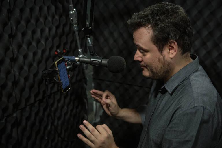 Homem fala para microfone enquanto olha para a tela de um celular