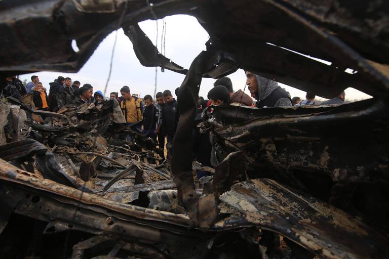 Palestinos observam um veículo destruído na cidade de Khan Younis, na faixa de Gaza, que o Hamas atribuiu ao bombardeio israelense