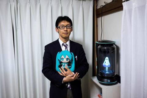 In this photograph taken on November 10, 2018 Japanese Akihiko Kondo poses next to a hologram of Japanese virtual reality singer Hatsune Miku as he holds the doll version of her at his apartment in Tokyo, a week after marrying her. - Akihiko Kondo, who is an administrator at a school, married to a Japanese virtual reality singer called Hatsune Miku in early November 2018. The bride is a computer animation with saucer eyes and lengthy aquamarine pigtails who performs to adoring fans as a hologram. (Photo by Behrouz MEHRI / AFP) / TO GO WITH AFP STORY: Japan-culture-entertainment-computers-music-social, FOCUS by Miwa SUZUKI