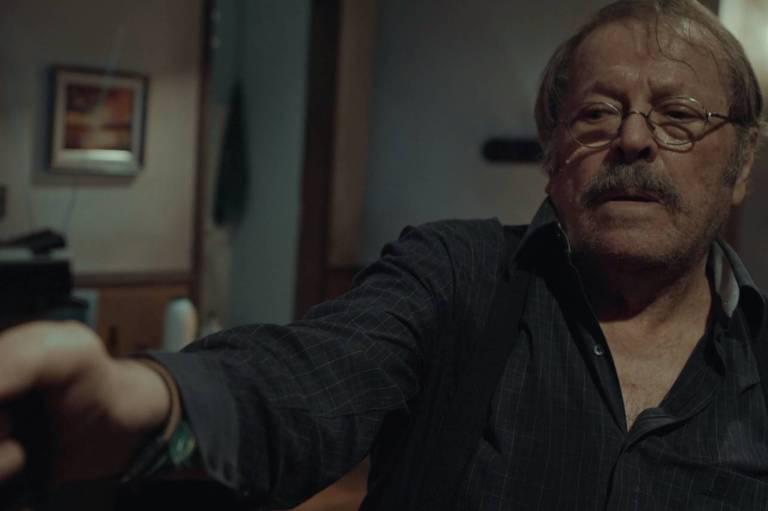 Carlos Vereza em quarto escuro, com cortinas vermelhas e aspecto antigo, apontando um revolver, não é possível ver quem está na mira da arma.