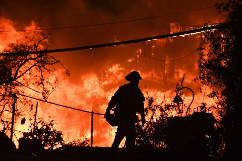 TOPSHOT - A firefighter is silhouetted by a burning home along Pacific Coast Highway (Highway 1) during the Woolsey Fire on November 9, 2018 in Malibu, California. - About 75,000 homes have been evacuated in Los Angeles and Ventura counties due to two fires in the region. (Photo by Robyn Beck / AFP)